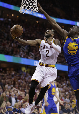 Cleveland Cavaliers guard Kyrie Irving (2) drives past Golden State Warriors forward Draymond Green during the second half of Game 3 of basketball's NBA Finals in Cleveland, Wednesday, June 8, 201 ...