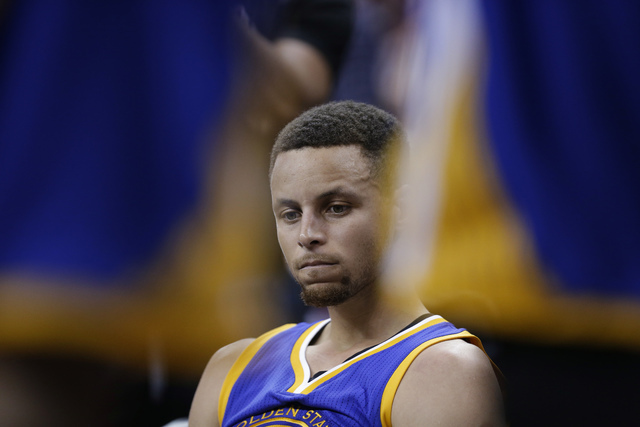 Golden State Warriors guard Stephen Curry sits on the bench during the second half against the Cleveland Cavaliers in Game 3 of basketball's NBA Finals in Cleveland, Wednesday, June 8, 2016. (Tony ...