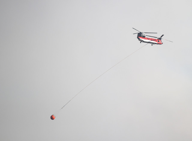 A helicopter aids in the effort to extinguish a brush fire in Yarnell, Ariz., Wednesday, June 8, 2016. T (Les Stukenberg/The Daily Courier via AP)