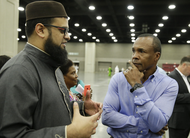 Safih Amed, left speaks with former boxing champion Sugar Ray Leonard before Muhammad Ali's Jenazah, a traditional Islamic Muslim service, in Freedom Hall, Thursday, June 9, 2016, in Louisville, K ...