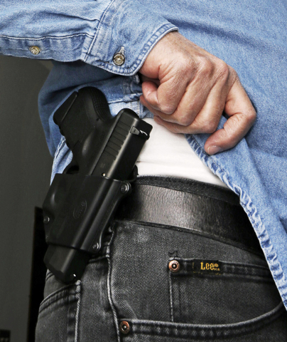 In this file photo Hank Johnson displays his handgun, in Springboro, Ohio. Dealing a blow to gun supporters, a federal appeals court ruled Thursday, June 9, 2016, that Americans do not have a cons ...