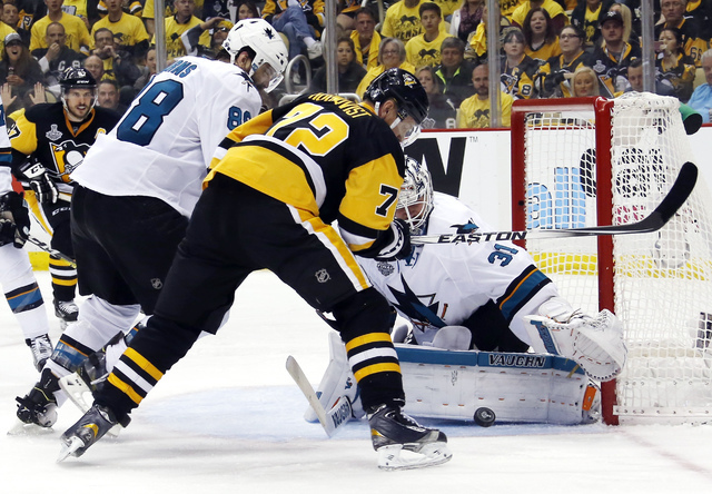San Jose Sharks goalie Martin Jones (31) turns a shot away as Pittsburgh Penguins' Patric Hornqvist (72) and Sharks' Brent Burns (88) scramble in front of the net during the third period in Game 5 ...