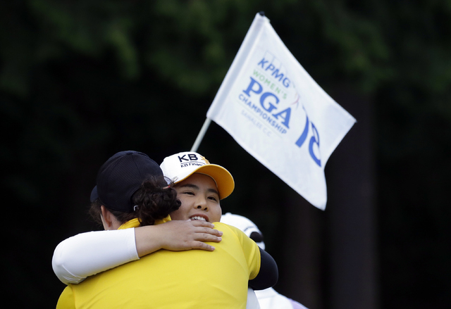 The flag for the 18th hole is carried past as Inbee Park, of South Korea, is embraced after finishing the first round at the Women's PGA Championship golf tournament at Sahalee Country Club Thursd ...