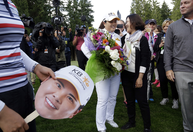 Inbee Park, center left, of South Korea, is embraced after finishing the first round at the Women's PGA Championship golf tournament at Sahalee Country Club on Thursday, June 9, 2016, in Sammamish ...