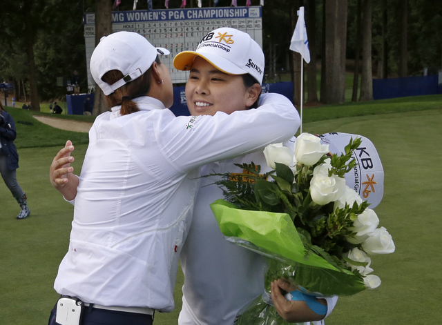 Inbee Park, right, of South Korea, is embraced after finishing the first round at the Women's PGA Championship golf tournament at Sahalee Country Club Thursday, June 9, 2016, in Sammamish, Wash. W ...