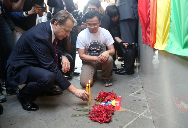 The U.S. ambassador to Thailand, Glyn T. Davies, places a candle with vigil organizer Paisam Likhitpreechakul outside the U.S. Embassy in Bangkok for those killed and wounded in the Sunday mass sh ...