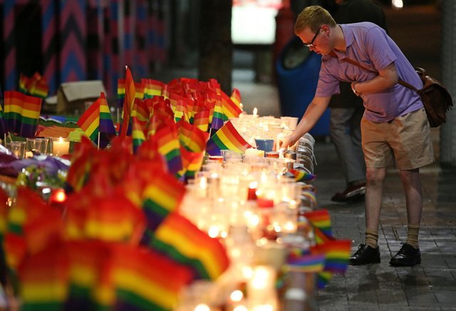 A man looks over an impromptu candlelit memorial set up in Sydney, Monday, June 13, 2016, following the Orlando, Florida, mass shooting where police say a gunman killed at least 50 people and woun ...