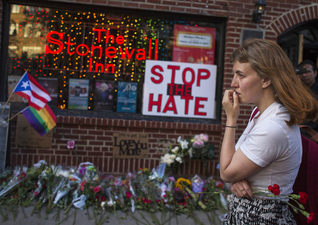 A woman cries and holds flowers in front of a makeshift memorial to remember the victims of a mass shooting in Orlando, Fla., in New York, Sunday, June 12, 2016. (Andres Kudacki/AP)