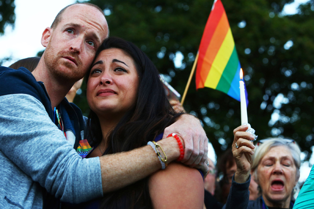 Jeffrey Erikson and Jamie Fernandez hold each other during a moment of silence at a vigil in Cal Anderson Park in Seattle for the victims of a mass shooting at Pulse nightclub in Orlando, Fla., Su ...