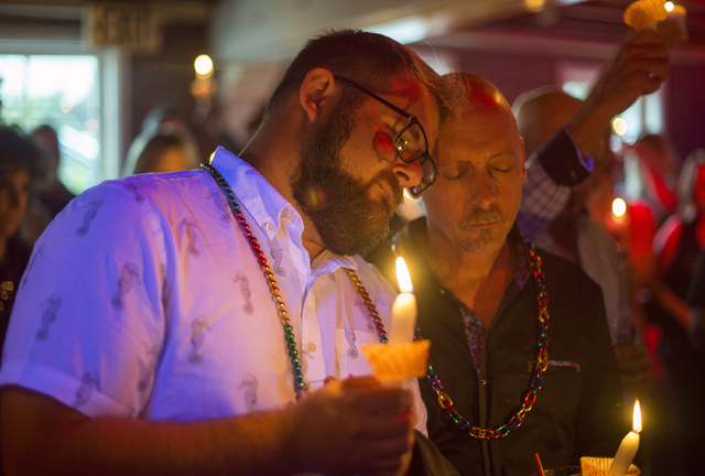 Don Haller, left, and Frank Thompson of Laguna Niguel pray for the victims of Orlando nightclub shooting at Main Street Bar in Laguna Beach, Calif., on Sunday, June 12, 2016. (Kyusung Gong/The Ora ...