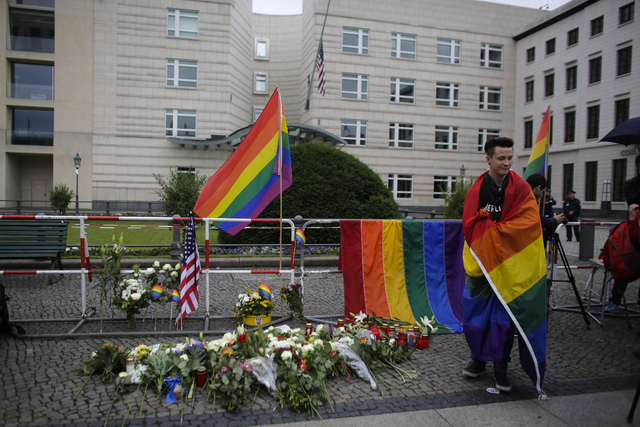 A man stand next to flowers placed in front of the U.S. embassy during a vigil in Berlin, Monday, June 13, 2016, to honor the victims of the attack on the gay nightclub in Orlando, Fla.  (Markus S ...