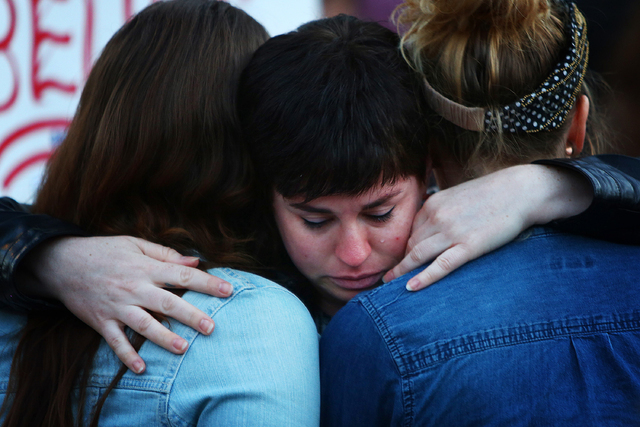 People embrace at a vigil in Seattle for the victims of a mass shooting at Pulse nightclub in Orlando, Fla., Sunday, June 12, 2016. (Genna Martin/seattlepi.com via AP)