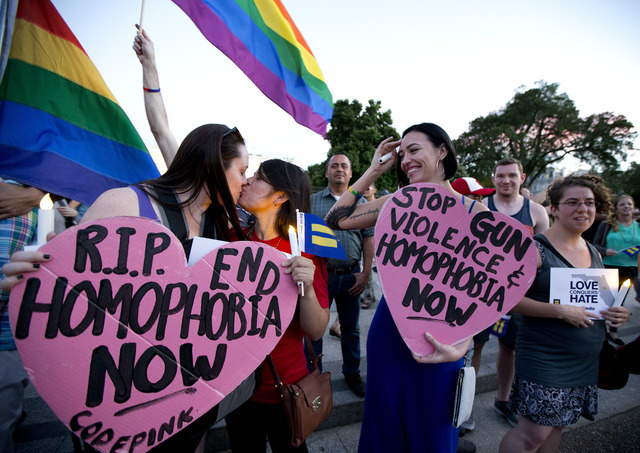 Rachel Henry, left, and Selene Arciga, kiss to show their solidarity with members and supporters of the LGBT gathered for a candlelight vigil in front of the White House in Washington, Sunday, Jun ...