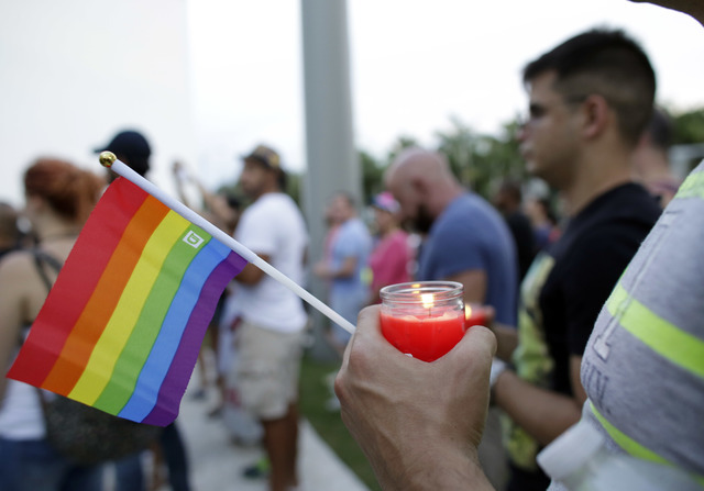 A man holds a candle and a rainbow flag during a vigil in memory of the victims of the Orlando mass shooting, Sunday, June 12, 2016, in Miami Beach, Fla.A gunman opened fire inside a crowded gay n ...