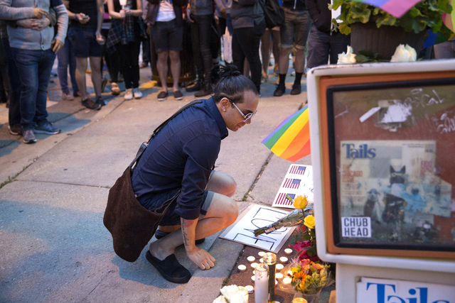 David Sotomayor, who is the cousin of Edward Sotomayor was among the victims, kneels at a makeshift memorial during a vigil for the victims of the Orlando nightclub shooting on Sunday, June 12, 20 ...