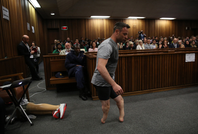 Oscar Pistorius' prosthetics lay on the floor as he walks on his stumps during argument in mitigation of sentence by his defense attorney Barry Roux in the High Court in Pretoria, South Africa, We ...