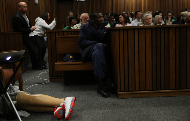 Oscar Pistorius' prosthetic lay on the floor as he walks on his stumps during argument in mitigation of sentence by his defense attorney Barry Roux in the High Court in Pretoria, South Africa, Wed ...