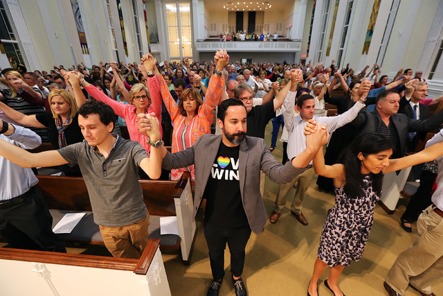 The congregation joins hands during an interfaith service at the First United Methodist Church of Orlando, Fla., Tuesday, June 14, 2016, for the dozens of people shot to death at a gay nightclub i ...