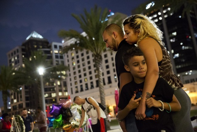 Jennifer Johnson, right, leans on her boyfriend, Jeansem Sambolin, while standing with her son Tyrone Clarke, 8, as they visit a makeshift memorial for the victims of the mass shooting at the Puls ...