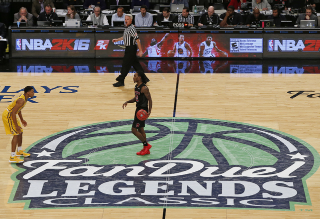 FILE - In this Nov. 24 2015, file photo, North Carolina State guard Anthony Barber dribbles the ball across the FanDuel logo during an NCAA college basketball game in the Legends Classic in New Yo ...
