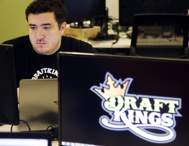 FILE - In this Sept. 9, 2015, file photo, Len Don Diego, marketing manager for content at the DraftKings daily fantasy sports company, works at his station at the company's offices in Boston. Draf ...