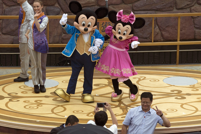Mickey and Minnie Mouse pose for a photograph at the opening ceremony for the Disney Resort in Shanghai, China, Thursday, June 16, 2016. Walt Disney Co. opened its first theme park in mainland Chi ...