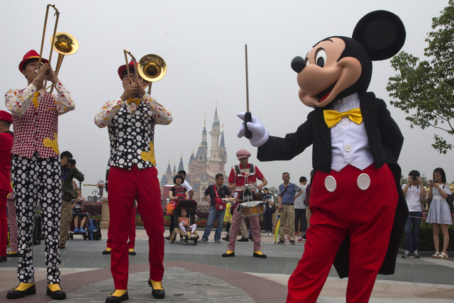 Mickey Mouse entertains visitors on the opening day of the Disney Resort in Shanghai, China, Thursday, June 16, 2016. Walt Disney Co. opened its first theme park in mainland China on Thursday. (Ng ...