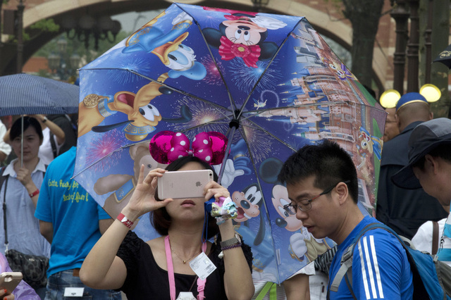A woman takes photo on her phone during the opening day of the Disney Resort in Shanghai, China, Thursday, June 16, 2016. Walt Disney Co. opened its first theme park in mainland China on Thursday. ...