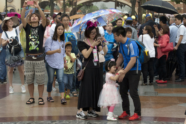 A child asks to be carried during a crowded opening day at the Disney Resort in Shanghai, China, Thursday, June 16, 2016. Walt Disney Co. opened its first theme park in mainland China on Thursday. ...