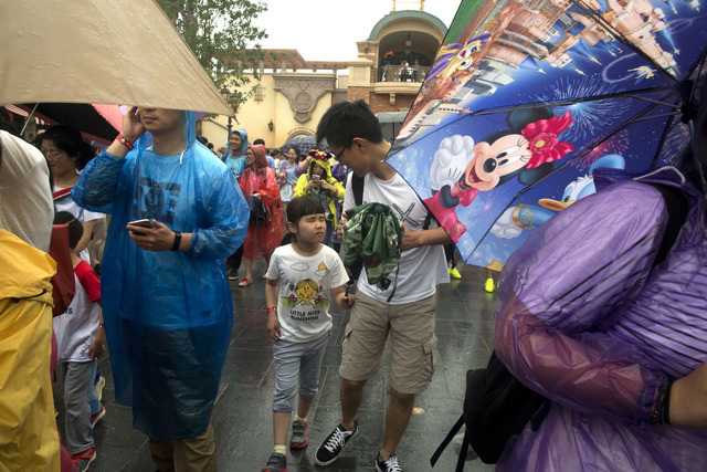 Visitors arrive on the opening day of the Disney Resort in Shanghai, China, Thursday, June 16, 2016. Walt Disney Co. opened its first theme park in mainland China on Thursday at a ceremony that mi ...