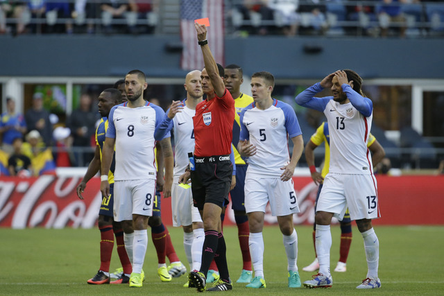 Referee Wilmar Roldan of Colombia, center, shows a red card to Ecuador's Antonio Valencia during a Copa America Centenario quarterfinal soccer match, Thursday, June 16, 2016 at CenturyLink Field i ...