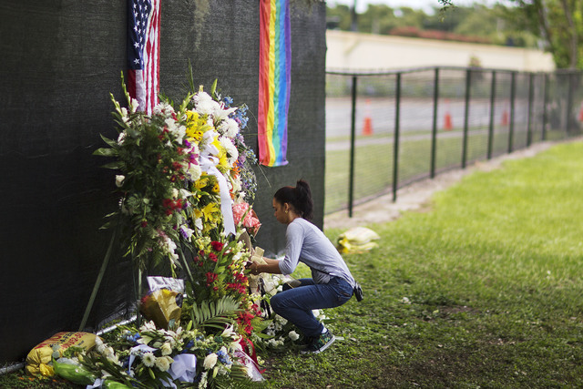 A mourner places flowers near the grave of Anthony Luis Laureano Disla, one of the victims of the Pulse nightclub mass shooting, following his burial service Friday, June 17, 2016, in Orlando, Fla ...
