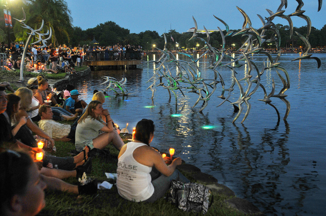 People hold candles at a candlelight vigil for the victims of the mass shooting at Pulse nightclub in Orlando, as they gather at Lake Eola Park in Orlando, Fla., Sunday, June 19, 2016. (Craig Ruba ...