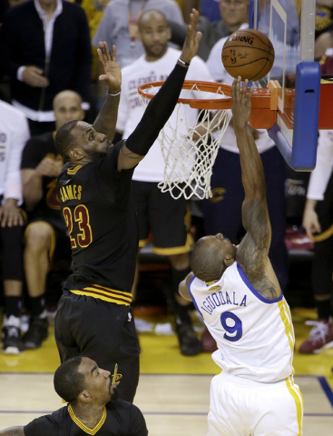 In this Sunday, June 19, 2016 photo, Cleveland Cavaliers forward LeBron James (23) blocks a shot by Golden State Warriors forward Andre Iguodala (9) during the second half of Game 7 of basketball' ...