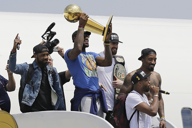 Cleveland Cavaliers' LeBron James holds up the NBA Championship trophy alongside teammates after arriving in Cleveland, Monday, June 20, 2016. (Tony Dejak/AP)
