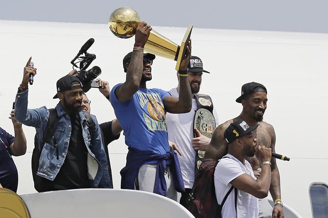 Cleveland Cavaliers' LeBron James holds up the NBA Championship trophy alongside teammates after arriving in Cleveland, Monday, June 20, 2016. (Tony Dejak/AP)