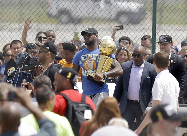 Cleveland Cavaliers' LeBron James carries the NBA Championship trophy after arriving in Cleveland, Monday, June 20, 2016. (Tony Dejak/AP)