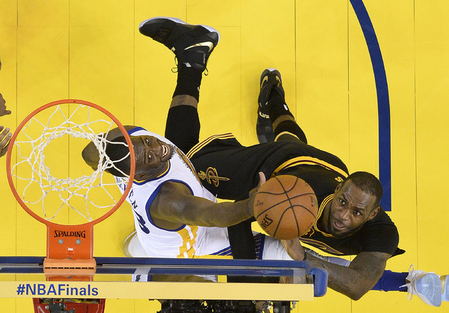 Cleveland Cavaliers forward LeBron James, right, shoots against Golden State Warriors forward Draymond Green during the second half of Game 7 of basketball's NBA Finals in Oakland, Calif., Sunday, ...