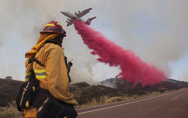 Upland Fire Capt. Joe Burna watches as a tanker drops fire retardant to stop a wildfire from jumping over Highway 94 near Potrero, Calif., on Monday, June 20, 2016. (Hayne Palmour IV/San Diego Uni ...