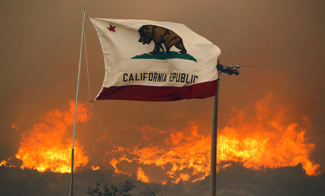 The California state flag flies next to a home on Highway 94 south Potrero, Calif., on Monday, June 20, 2016, as huge flames roar behind it. An intensifying heat wave stretching from the West Coas ...
