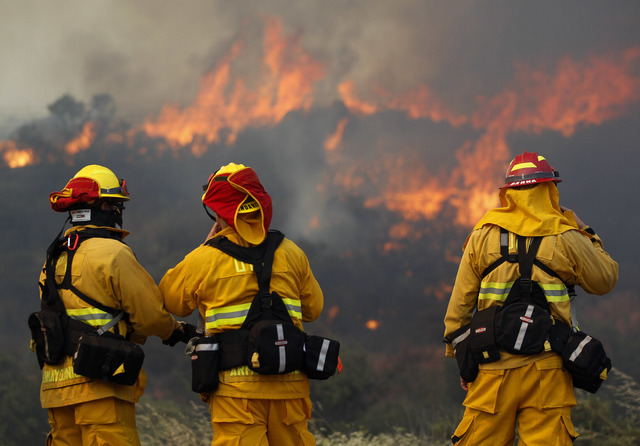 Upland firefighters, from left, Nima Homayounieh, Joseph Armendariz, and Capt. Joe Burna, watch as flames burn toward Highway 94 near Potrero, Calif., on Monday, June 20, 2016. (Hayne Palmour IV/S ...