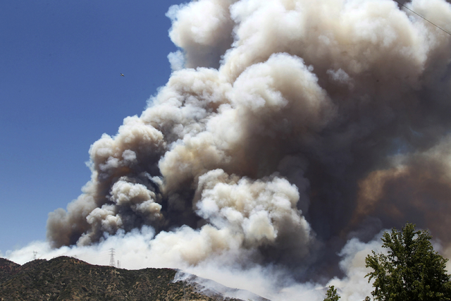A large plume of smoke from a wildfire rises above a hillside just north of Azusa, Calif., Monday, June 20, 2016. New wildfires erupted in Southern California as an intensifying heat wave stretchi ...