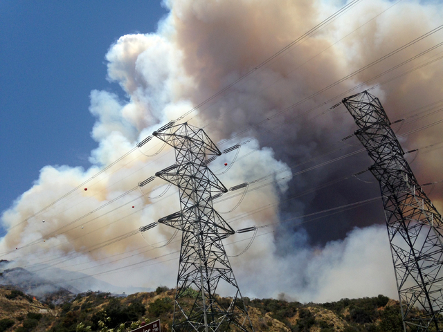 Smoke from a wildfire rises from a hillside near power lines outside of Azusa, Calif., Monday, June 20, 2016. Two fires have erupted in the San Gabriel Mountains northeast of Los Angeles amid with ...