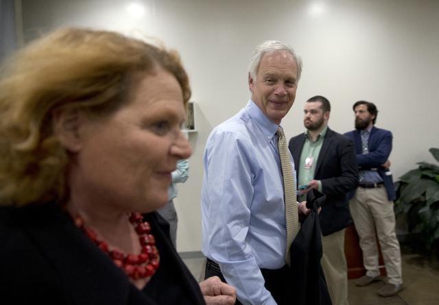 Senators Heidi Heitkamp, D-N.D., left, and Sen. Ron Johnson, R-Wis., walk towards the Senate on Capitol Hill, Monday, June 20, 2016 in Washington. A divided Senate hurtled Monday toward an electio ...