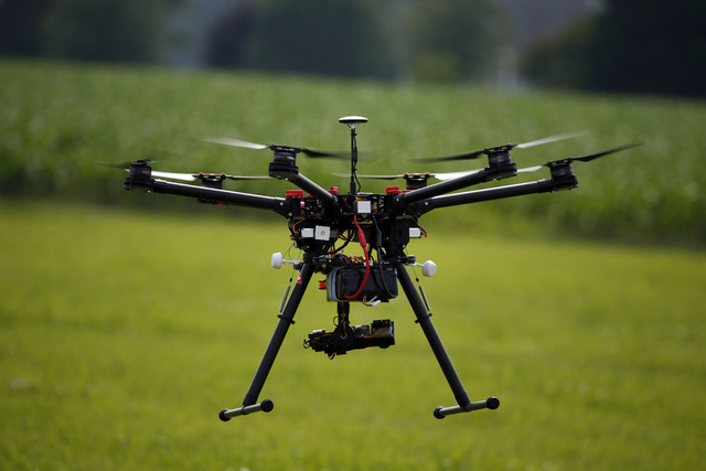 A hexacopter drone is flown during a drone demonstration at a farm and winery on potential use for board members of the National Corn Growers, Thursday, June 11, 2015 in Cordova, Md. Routine comme ...