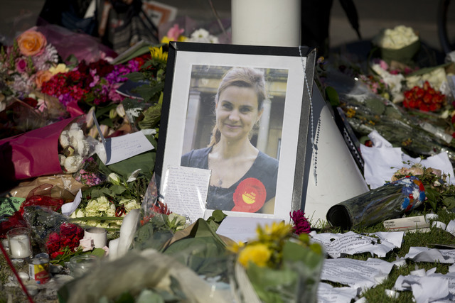 A photograph of Jo Cox, the 41-year-old Member of Parliament fatally shot last week in northern England, stands amongst tributes laid in her memory in Parliament Square, London, after a service of ...