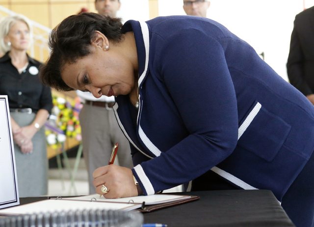Attorney General Loretta Lynch writes in a book at City Hall expressing sympathy and condolences to the victims of the Pulse nightclub mass shooting, Tuesday, June 21, 2016, in Orlando, Fla. (John ...