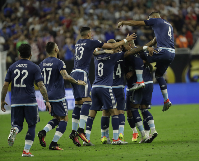 Argentina midfielder Lionel Messi is surrounded by teammates after scoring a goal against the United States during a Copa America Centenario semifinal soccer match Tuesday, June 21, 2016, in Houst ...