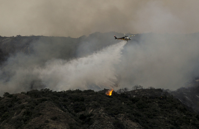 A firefighting helicopter makes a water drop on a hill near a wildfire in Duarte, Calif., Tuesday, June 21, 2016. Surging wildfires on Tuesday forced new evacuations of hundreds of homes across th ...