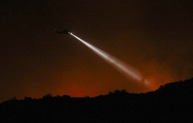 A firefighting helicopter prepares to make a water drop on a wildfire in Duarte, Calif., Tuesday, June 21, 2016. Firefighters worked to make gains against Southern California wildfires as an inten ...